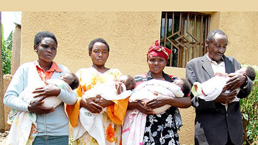 Nyirakanyana (2nd R) and her husband together with their older daughters hold the quadruplets. The New Times/ Courtesy.