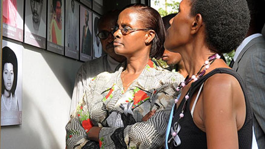 Relatives of victims of the 1994 Genocide against the Tutsi look at the pictures of their departed ones at Kigali Genocide Memorial Centre. The New Times/ J. Mbanda.