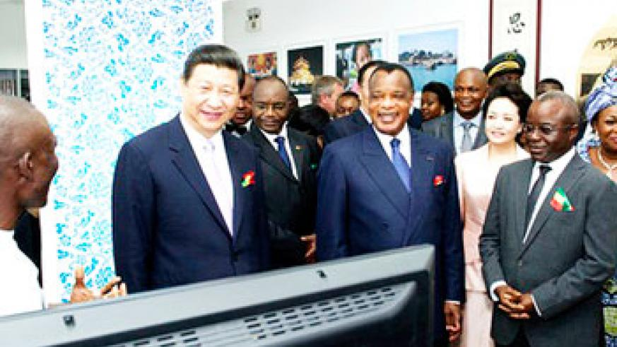 Chinese President Xi Jinping (2nd L) listens to an IT geek in Congo Brazzaville during his recent tour of the continent. Jinping said the with the global economy undergoing profound an....