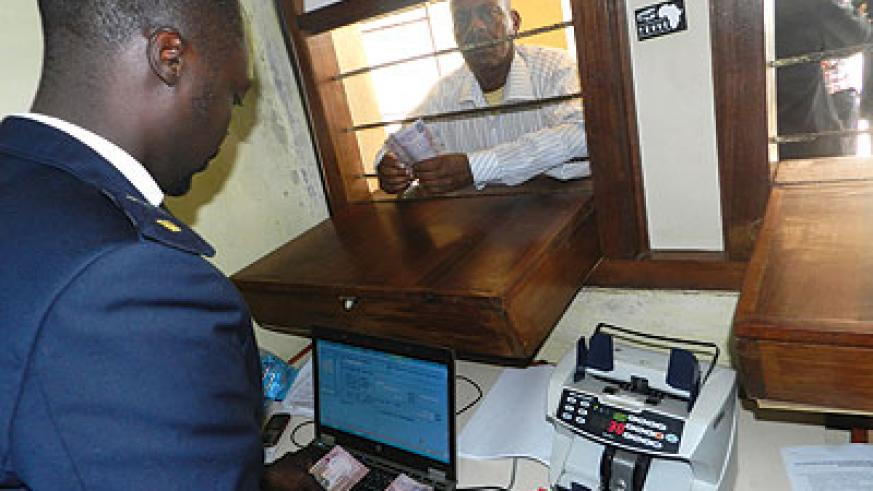 A man pays tax at Rusumo customs point. Expanding the tax base could help cut dependence on aid.  The New Times / File photo