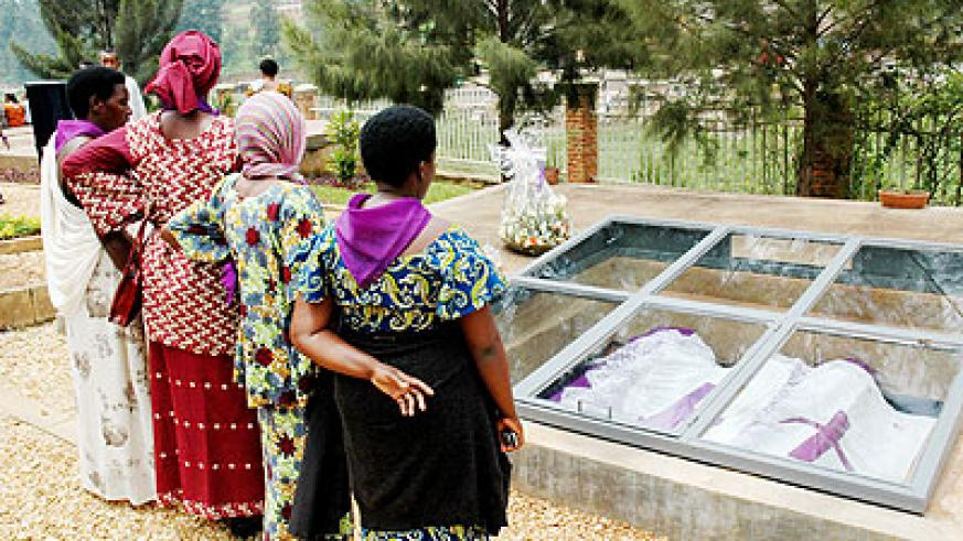 Survivors meditate by a mass grave at the Kigali Genocide Memorial Centre recently. The New Times/ John Mbanda.