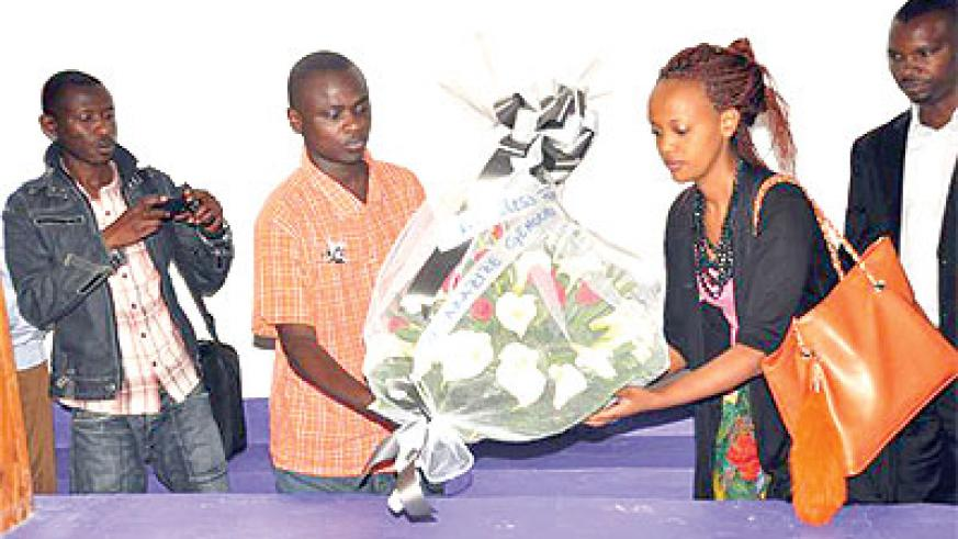 Knowless (R) lays a wreath at the Nkomero Genocide memorial in the Southern Province. Courtesy photos.