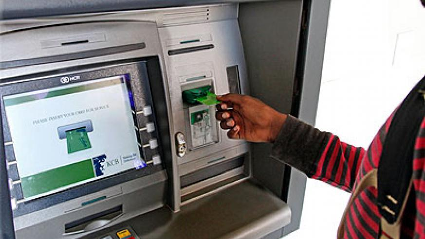 A bank client uses an automated card. The New Times / T. Kisambira.