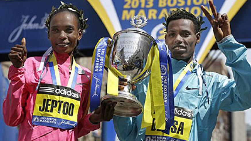 Rita Jeptoo of Kenya and Lelisa Desisa of Ethiopia pose with a trophy at the finish line after winning the women's and men's divisions of the 2013 Boston Marathon. Net photo.