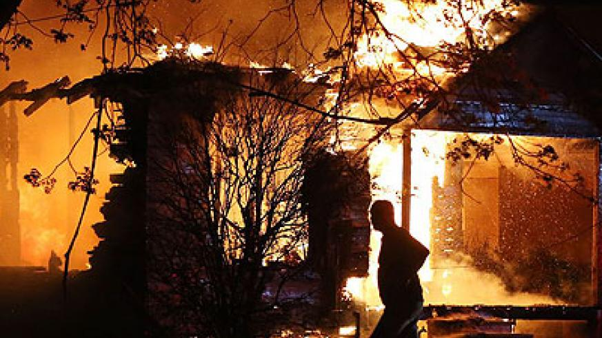 A man is silhouetted by blaze ravaging a home in the vicinity of the Waco blast zone. There were no immediate official comments on what may have sparked the fire or what led to the mas....