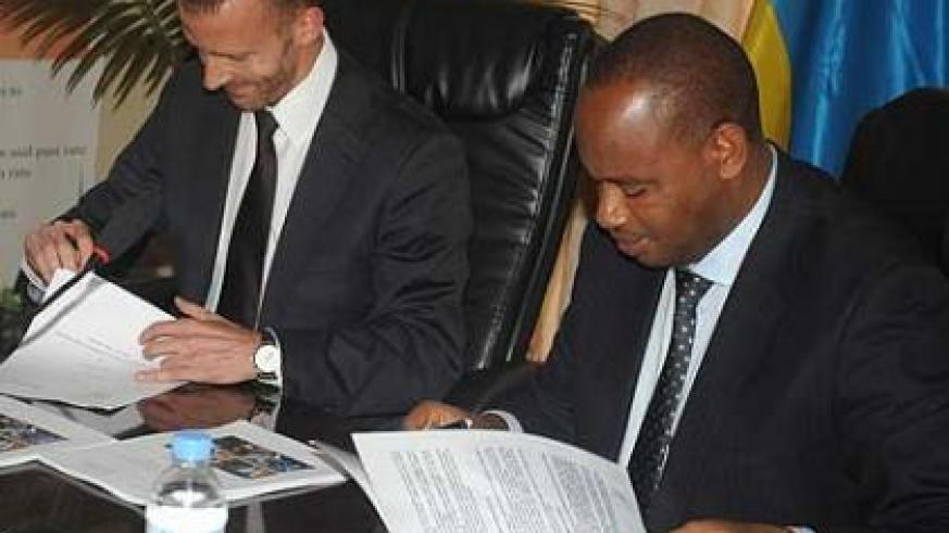 Nsengiyumva (R) and Flueckiger sign the Cooperation Agreement on Thursday. The New Times/John Mbanda