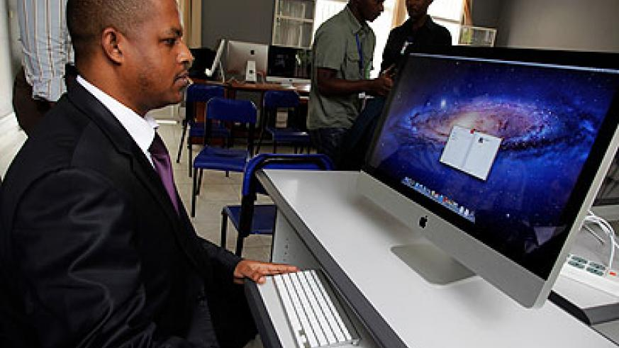 Gasana tests one of the new iMac Computers to be used at Rwanda Media Academy.    The New Times/ Timothy Kisambira.