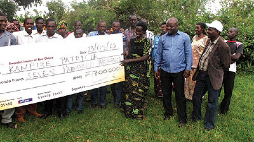 Kampire (second, right) receiving a dummy cheque of her compensation on Thursday. The New Times / Stephen Rwembeho