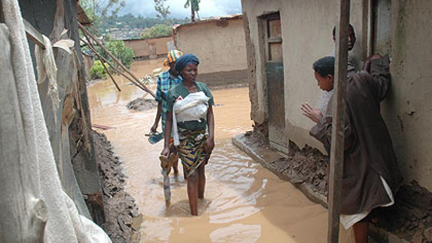 Women wade through flood water in Rwaza last year. Residents evacuated from the area say they need more assistance.  The New Times/ File.