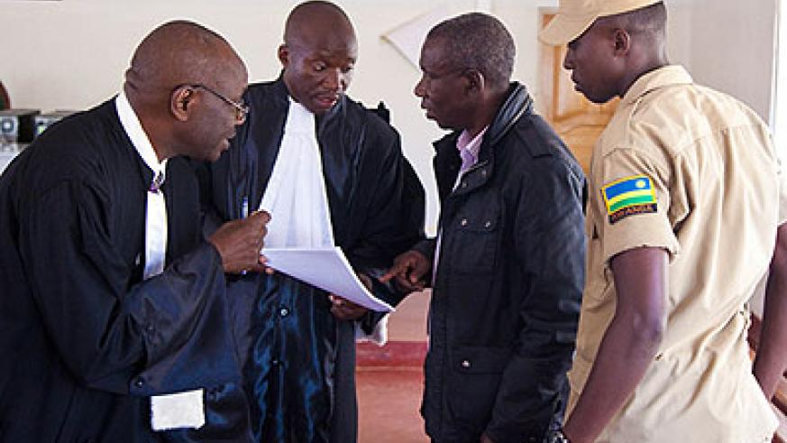 Bandora ( 2nd R) talks to his lawyers Boniface Nizeyimana (C) and Mbera Ferdinand (L) after the hearing.  The New Times/ Timothy Kisambira.