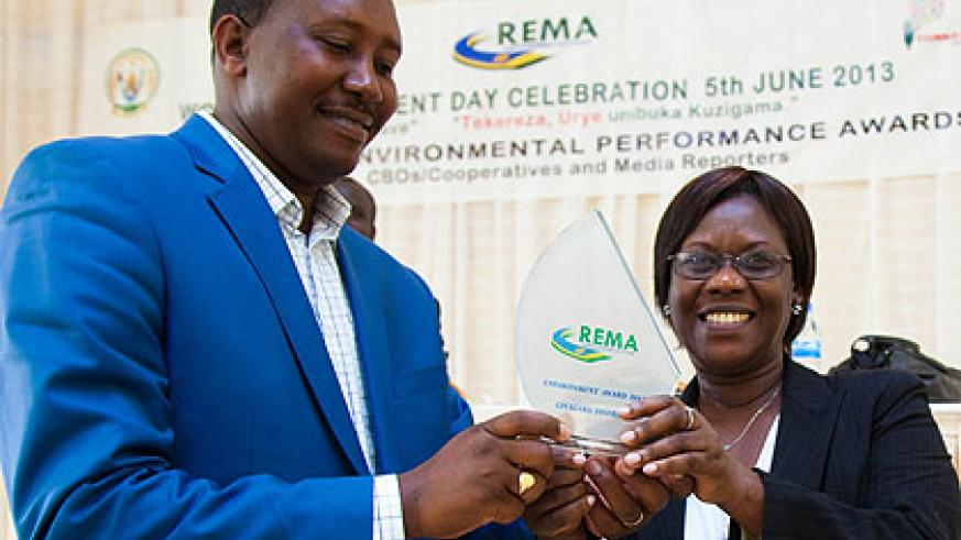Leandre Karekezi (L), the mayor of Gisagara, receives an award his district won for protecting the environment from State Minister for Social Affairs, Dr Alvera Mukabaramba, yesterday. The New Times / Timothy Kisambira
