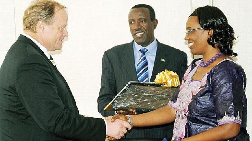 Dirk Niebel (L), the German Federal Minister for Economic Cooperation and Development, receives gifts from Speaker Rose Mukantabana and Senate President Jean Damascène Ntawukuriryayo at Parliament Building.