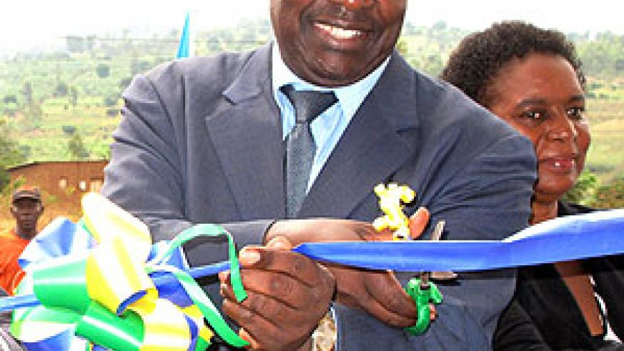 Min. Francis Kanimba cutting a ribbon to officially open one of the SACCOs. Sunday Times / S. Rwembeho.