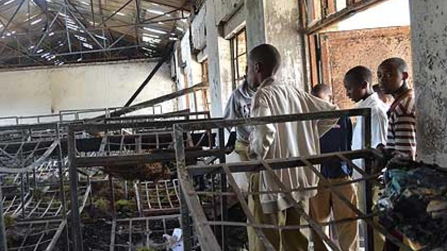 Students stare at what remained of a dormitory after one of the fires gutted Byimana School of Sciences. The New Times/ File.