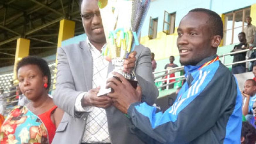 Sports Minister Protais Mitali gives the trophy to AS Kigali skipper Jimmy Mbaraga after the 3-0 win over AS Muhanga at Amahoro Stadium. Sunday Times/Courtesy