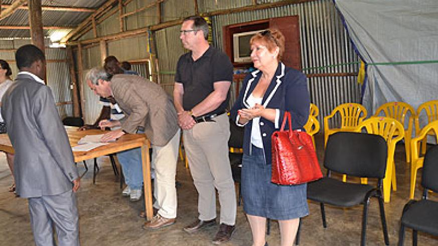 One of Belgian MPs signs a visitor's book after the tour in Mutobo. The New Times/ Jean Mbonyinshuti.