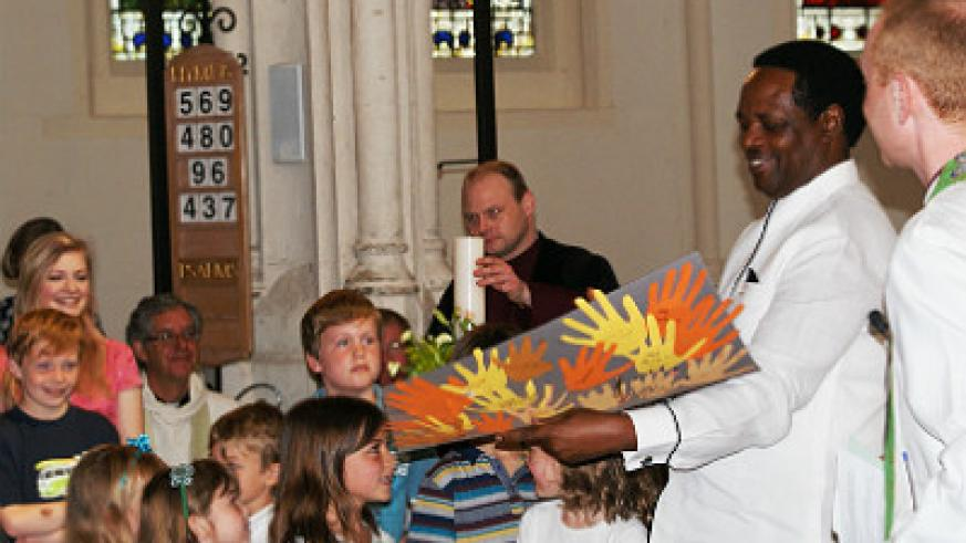 H.E Nkurunziza with children at St Edmunds Cathedral presenting him with an art piece done by them entitled Hands of Friendship to mark the day residents of Bury St. Edmunds, declared ....