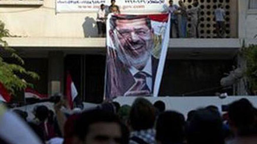 Mohammed Morsy supporters holding placards to demand his immediate reinstatement outside the Presidential Guard barracks where the Egyptian former leader is thought to be held. Net photo.