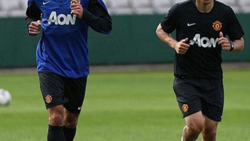 Straight into the action- Robin van Persie warms up alongside United coach Phil Neville in Sydney, hours after arriving for the second leg of the club's pre-season tour.  Net photo.