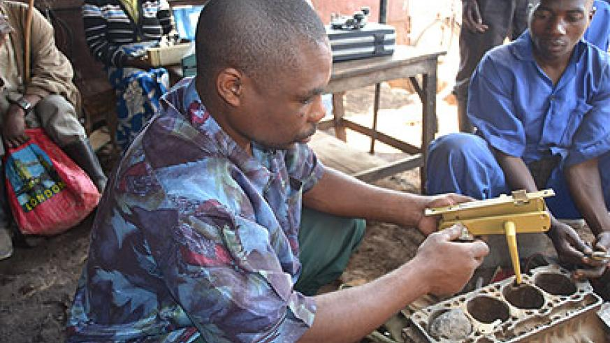 Ndabateze,  tests a key he has finished fabricating.  The New Times/Jean d'Amour Mbonyinshuti.