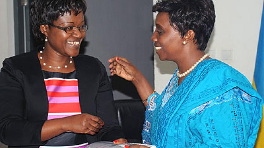 Former EAC affairs Minister Monique Mukaruliza (L) hands over to her successor, Muhongayire yesterday. The New Times/John Mbanda