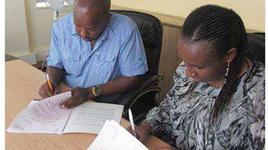 Joseph Mukama, the director of Rusororo Aggregate  and Fusion's Kageenu sign the deal. Courtesy photo