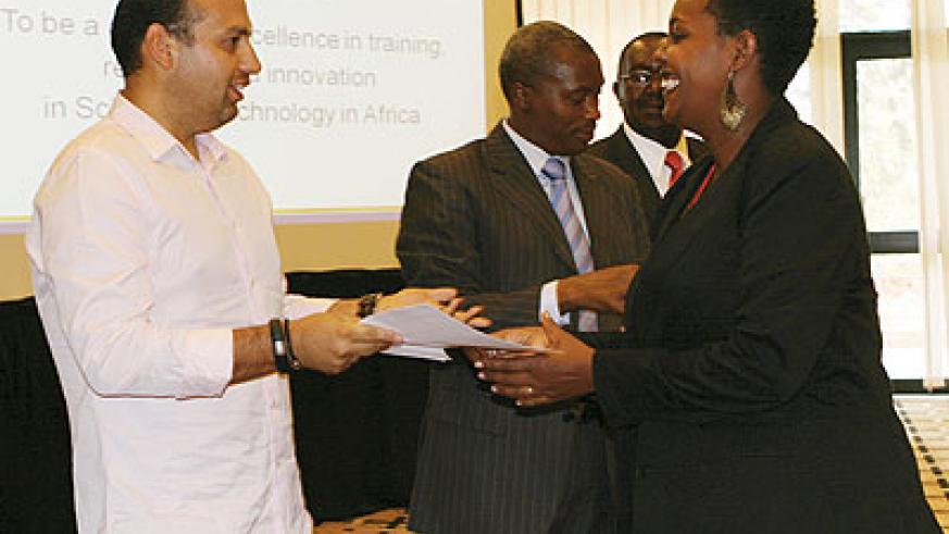 Camberos (left) handing over a certificate to one of the 18 students who were awarded MBAs last week. The New Times / Peterson Tumwebaze