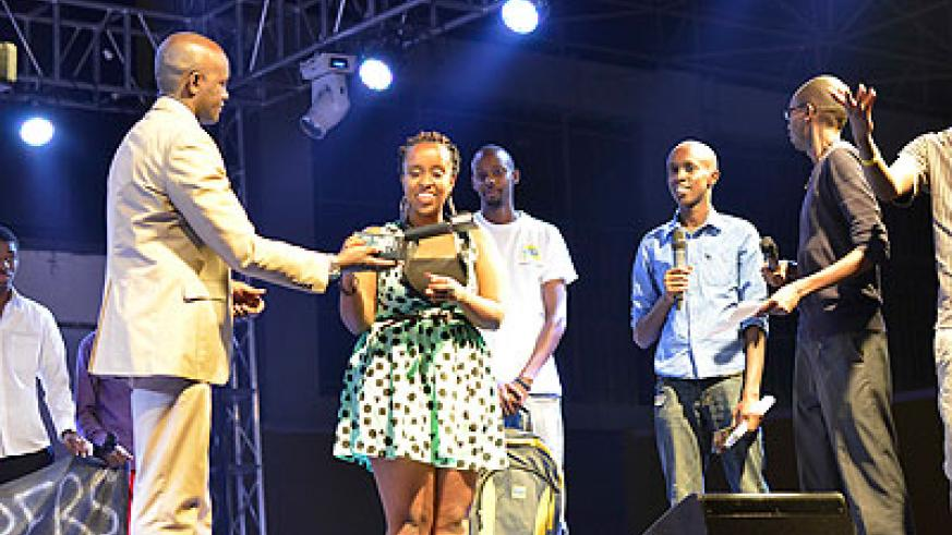 Teta picks up her award as other winners look on.