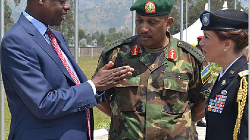 Minister Kabarebe, Chief of Defence Staff General Patrick Nyamvumba and the US Military Attaché, Lt Col Gwyn A. Carver, chat after the official opening of  the Senior Staff Course yes....