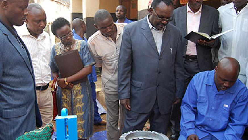Kanimba (C) gets closer to inspect Nteziryayo's technical expertise in electronics and machinery repair during his tour of SMEs in Rulindo District on Tuesday. The New Times/Jean d'A....