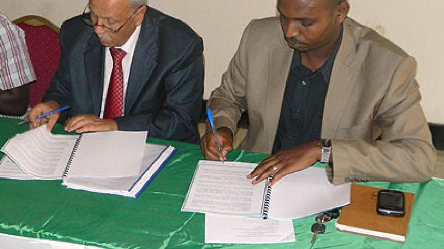 Tunisia Volleyball Federation chairman Mr. Mounir Ben Slimane and FRVB Chairman Gustave Nkurunziza signing the agreement yesterday in Kigali. The New Times / P. Kamasa.
