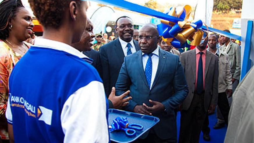 Premier Pierre Habumuremyi is briefed just before he cuts the ribbon to launch Expo 2013 yesterday.