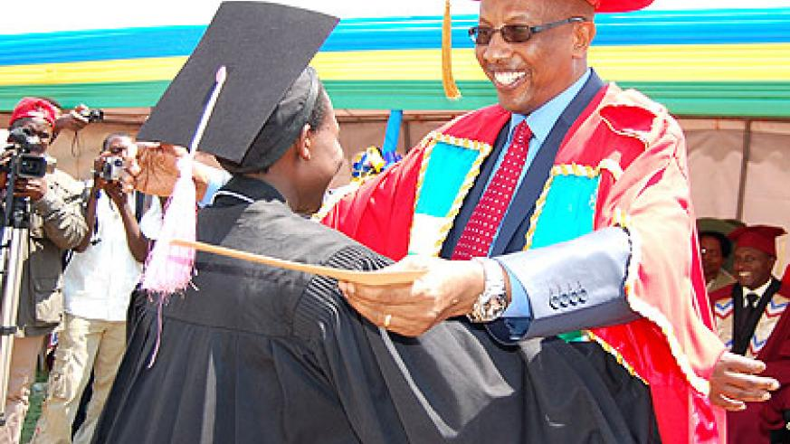 Acting Executive Director for the National Council of Higher Education, Dr. Innocent Mugisha, congratulates the best student. Saturday Times/Stephen Rwembeho.