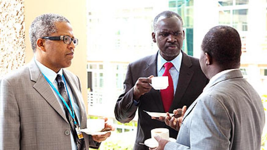 Desanker (L) and Kamanzi (C) listen to Tanzania's Richard Muyugi, the chairperson of UNFCCC, during coffee break at the conference yesterday. The New Times/ T. Kisambira.