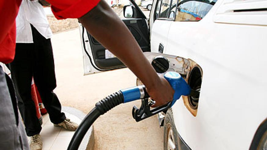 A fuel pump attendant fills a car. Prospecting oil in the country will be a major step in boosting the country's oil sector.   The New Times/ File.