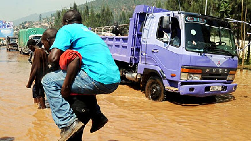A man is carried across a flooded Nyabugogo highway after a downpour. Flooding will be minimal this rainy season. The New Times/File