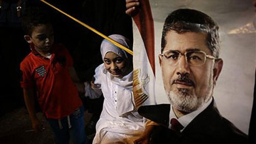 An egyptian child stands next to poster of the Egypt's ousted President Morsi. Net photo.
