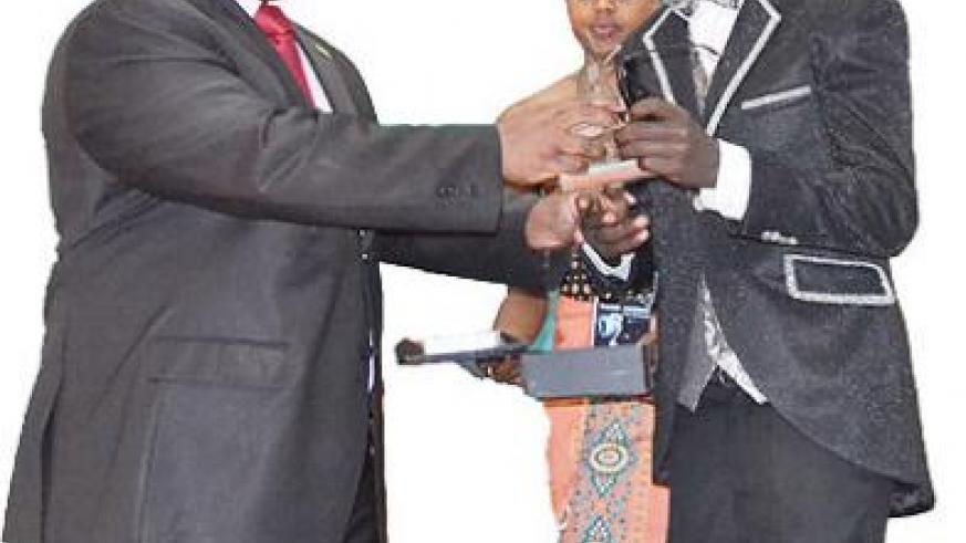 The Governor of Northern Province Aime Bosenibamwe (L) presents the award Franc Kay for the Best Male Artiste. The New Times / Jean d'Amour Mbonyinshuti.