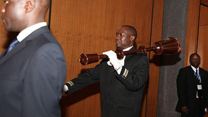 An EALA Sergent at Arms carries the mace to during a session in Kigali.  The Assembly is divided on whether or not sessions should continue to be alternated within partner states. The ....