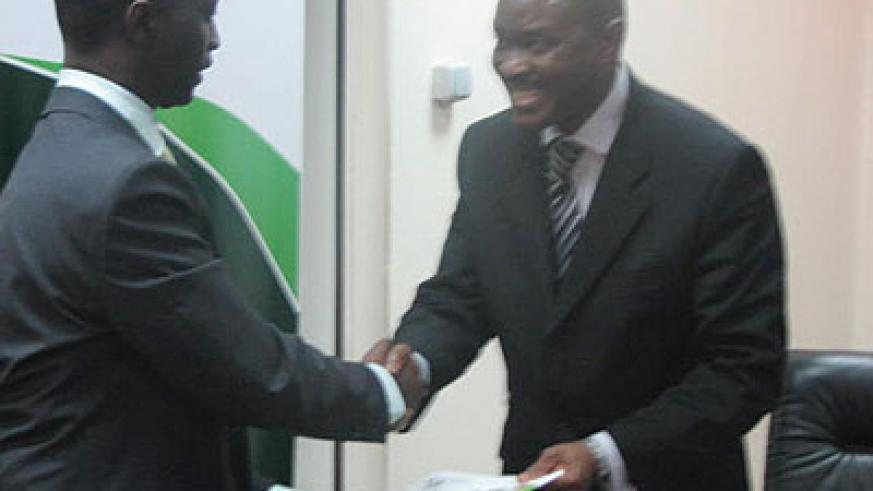 Kanyankore and Yaovi exchange the documents. The New Times / Ben Gasore