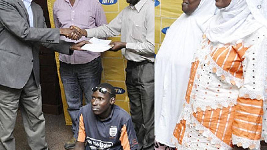 LEFT: Sheikh Iyakaremye (R) receives the cheque from Uwizeye at the MTN headquarters in Nyarutarama on Wednesday, as Muslim youth foundation officials look on (right). The New Times/ T....