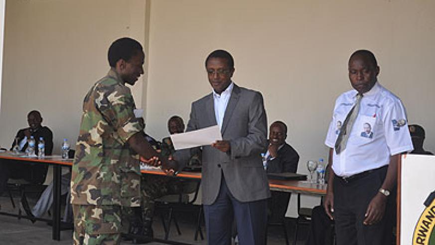 Dr Biruta (R) awards a certificate to one of the participants at this year's Itorero training. The minister urged the youth to remember their debt to the country. The New Times/ Iren....