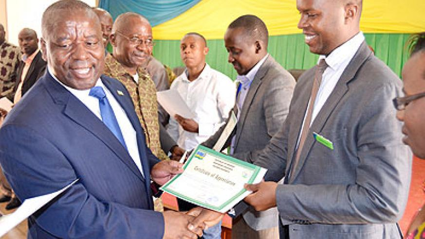 Bosenibamwe (L) awards a certificate of appreciation to Rulindo best performers. The New Times/ Jean Mbonyinshuti.