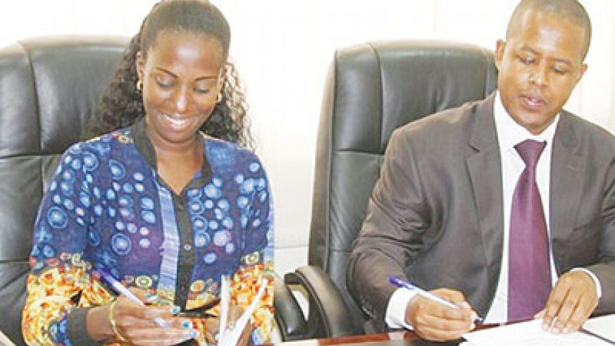 The Director General of WDA Jerome Gasana (R) and Belinda Umurerwa (L) from the Digital Media Group studio signing the MoU. The New Times / Courtesy.
