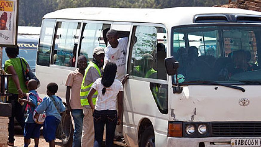 Passengers board a mini-bus at Gisementi stage in Remera. A new transport policy in the City of Kigali will soon be rolled out after three transport operators won bids to manage specif....
