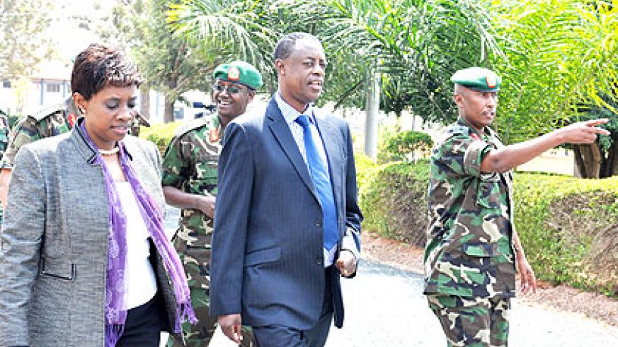Col. Denis Rutaha, the commandant of the RDF Combined Training Centre , Gabiro, (R) takes top officials, including ministers Muhongayire (EAC affairs), Kabarebe (defence) around the ce....