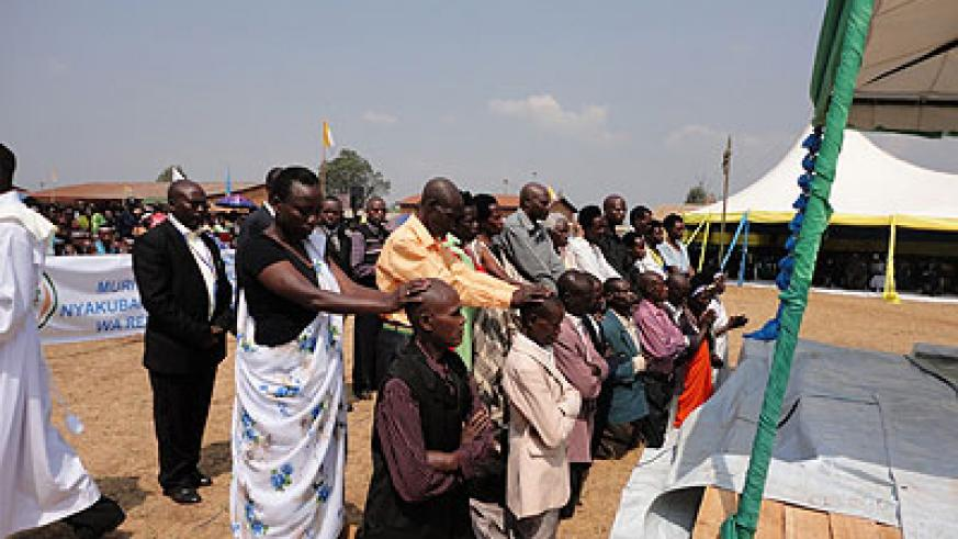 Ten Genocide convicts (kneeling) reconciled with relatives (standing) of those they killed after attending a reconciliation programme. Saturday Times/JP Bucyensenge