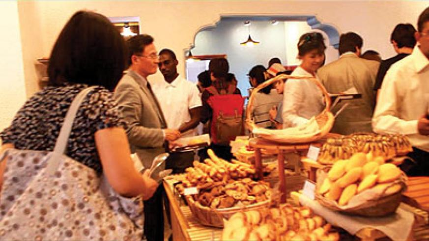 Some of the guests at the opening of the coffee shop serve themselves eats. The New Times / Collins Mwai