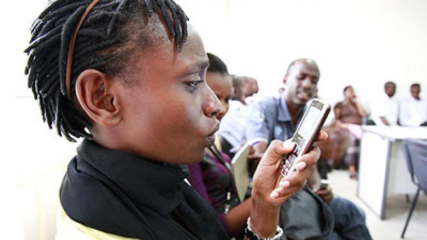 A lady reads a text message on her mobile handset. The New Times/ File.