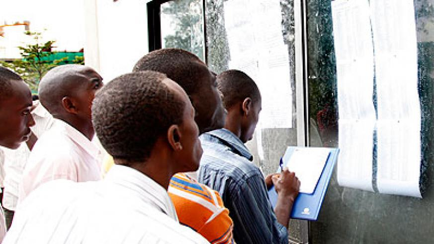 Students at the School of Finance and Banking check their marks on the notice board.  The New Times/ File.